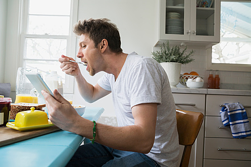 Man eating cereal and using digital tablet kitchen